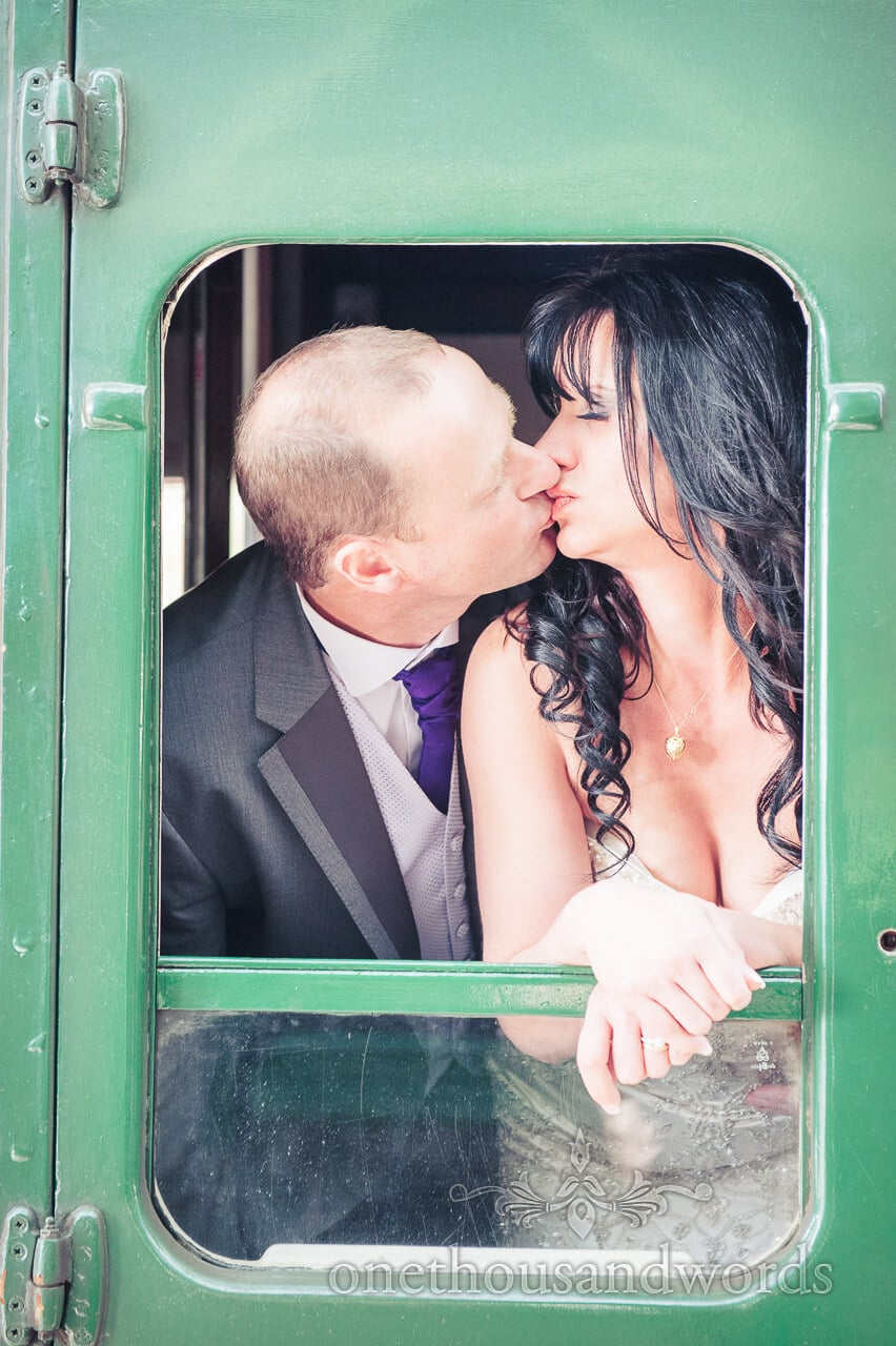 Bride and groom kiss on Corfe Castle wedding Steam Train