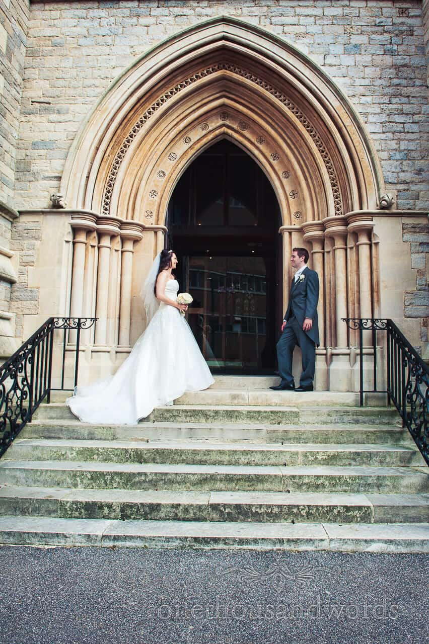 Bride and Groom on the steps with stone arched church doorway