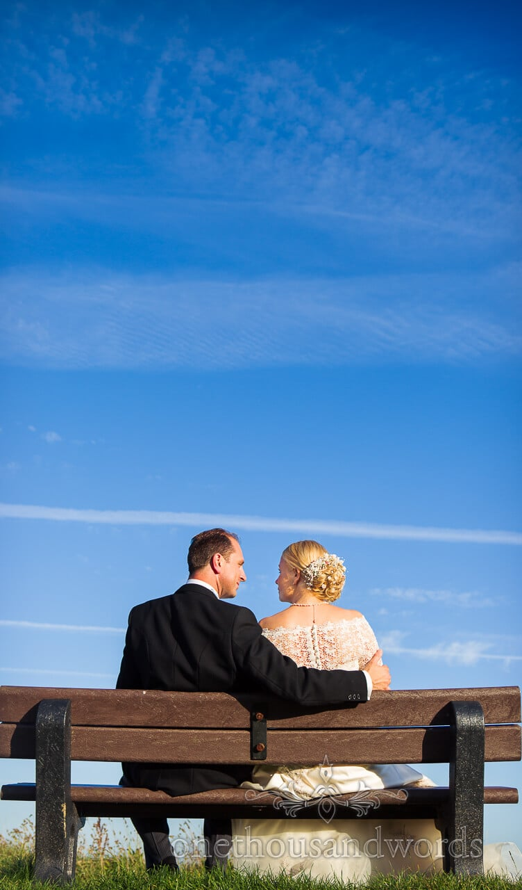 Bride and groom sat on bench with blue sky