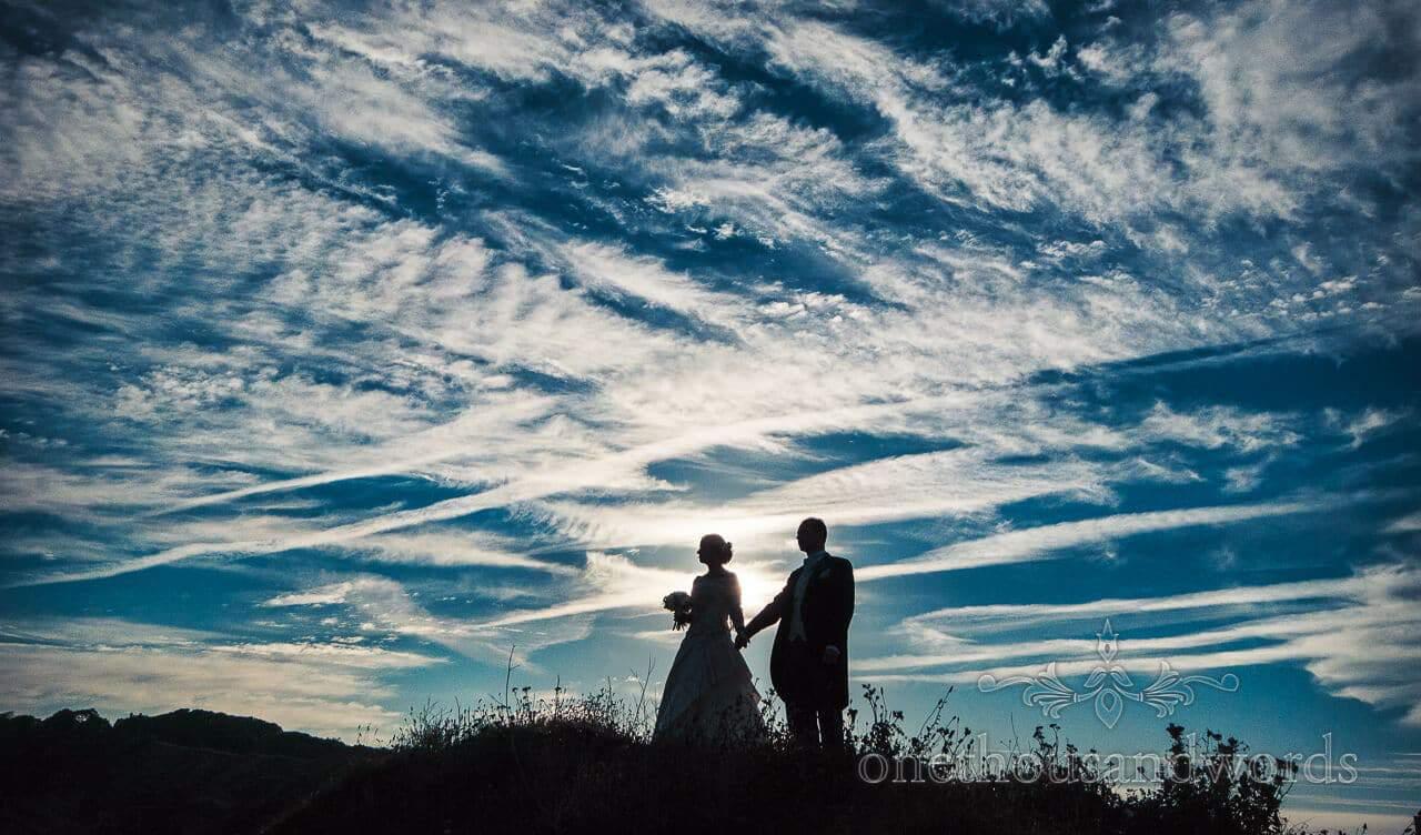 Bride and groom shilouette agains amazing sky at Durslton Castle Wedding