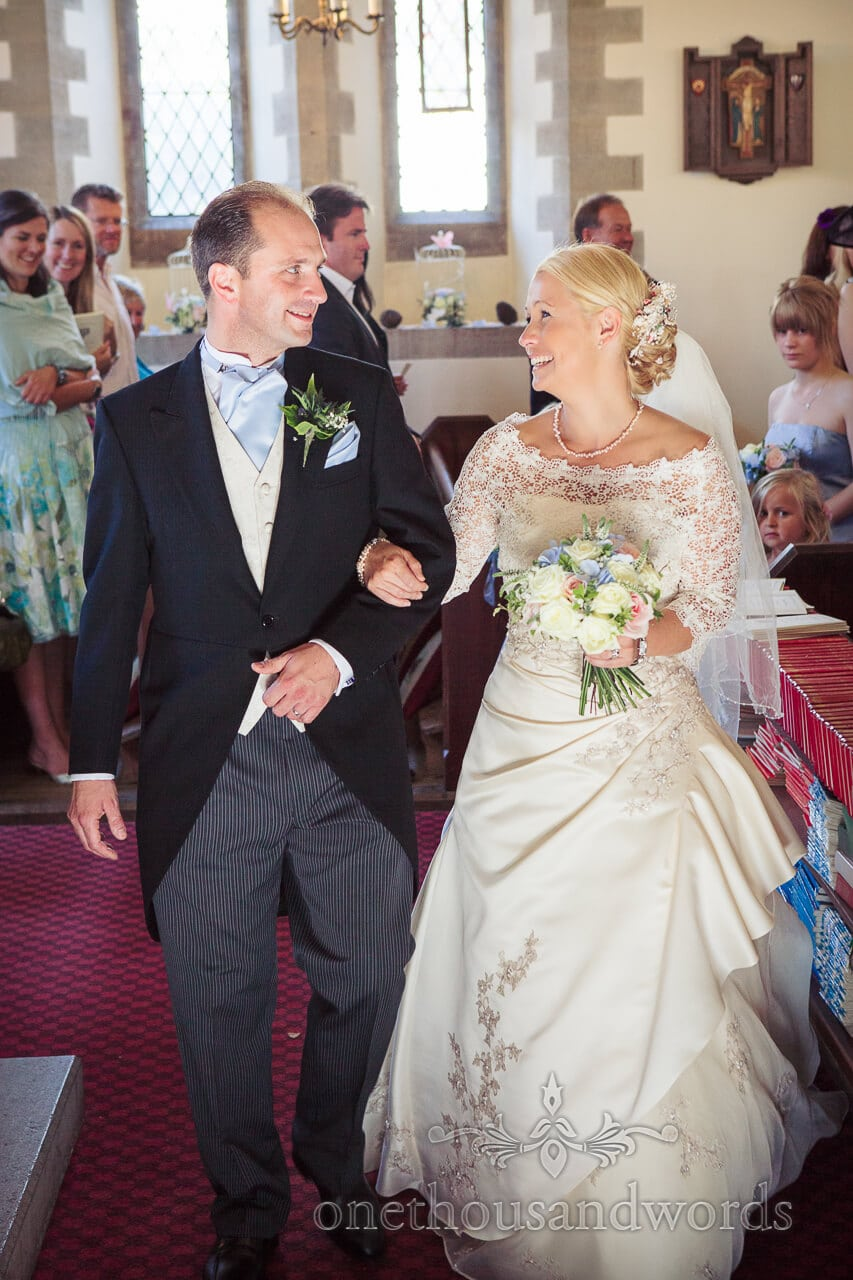 Bride and groom smiling as they leave Swanage church wedding service