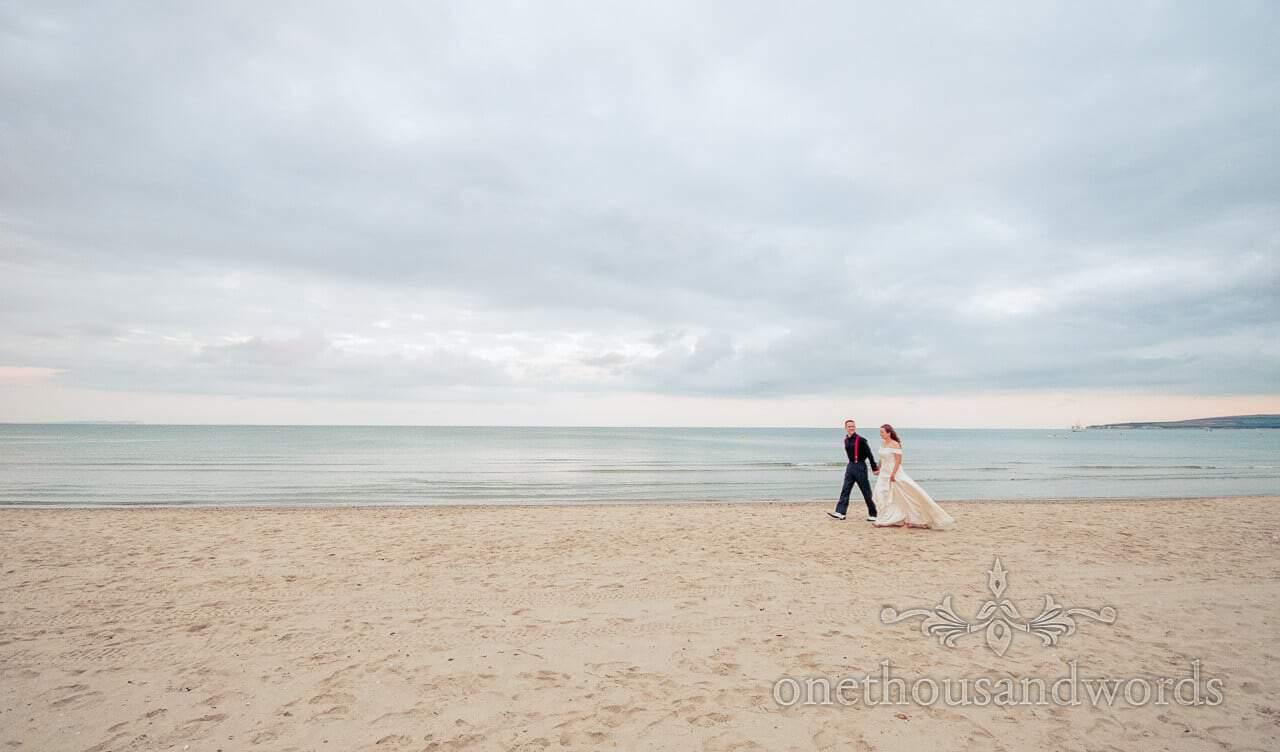 Bride and groom walk on Sandbanks Beach