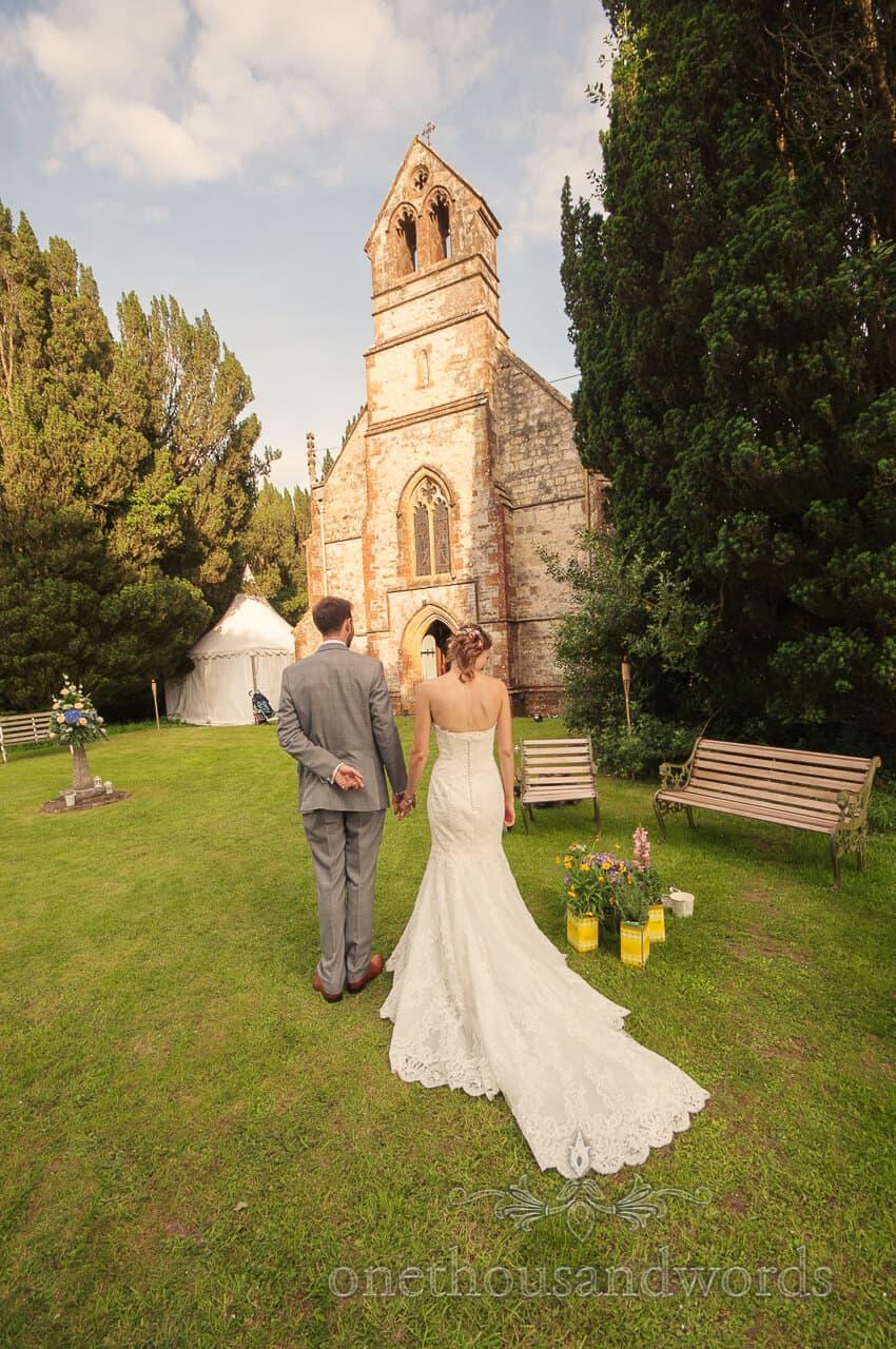 Bride and groom walk to church wedding breakfast at Plush Manor, Dorset