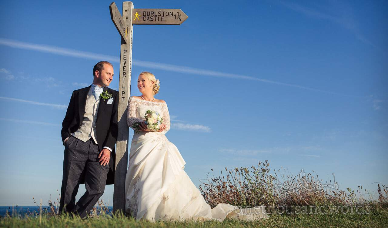 Bride and groom with wedding signpost for Durlston Castle wedding venue