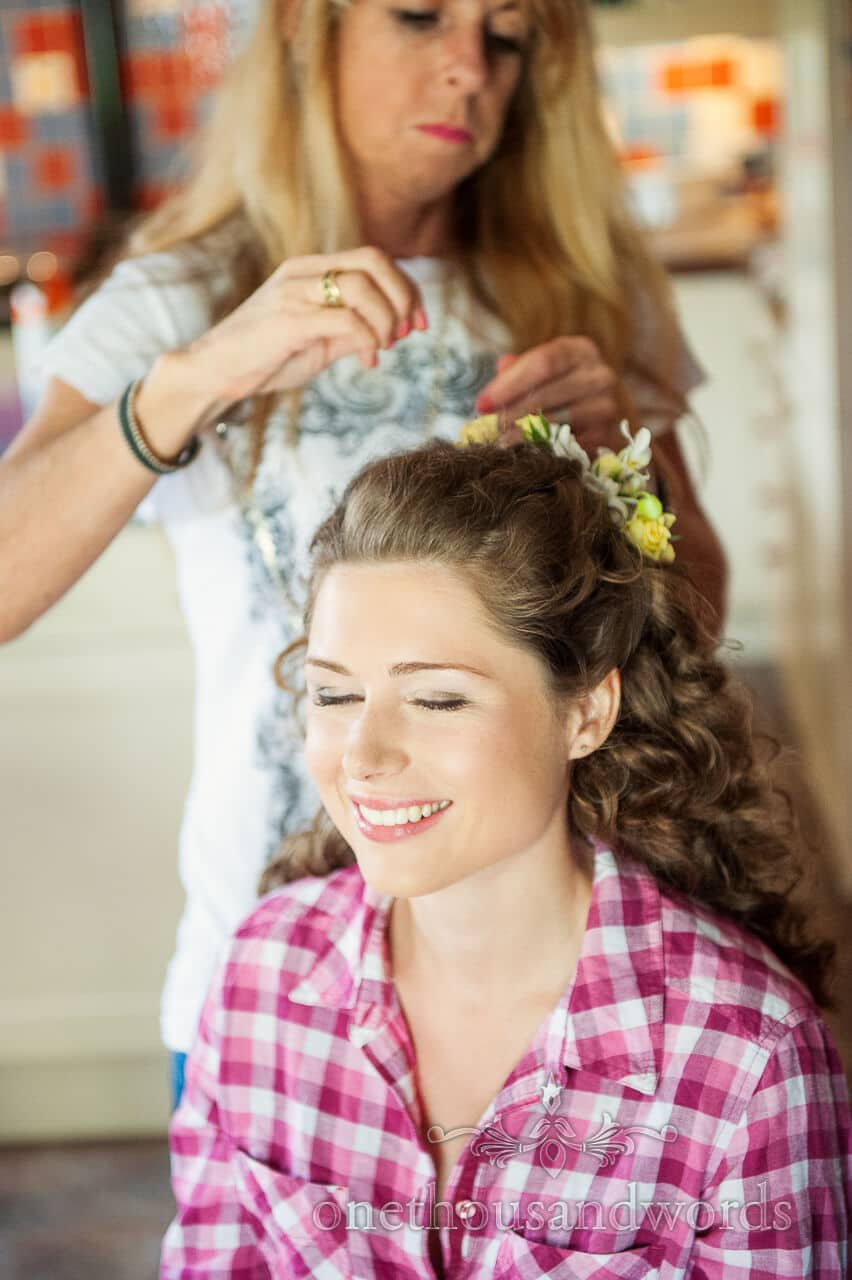 Bride has flowers added to her hair on wedding morning