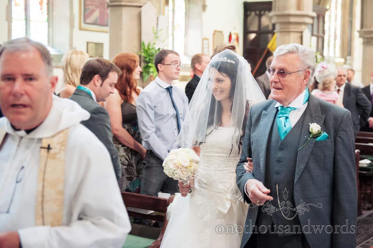 Happy bride under veil walks down the aisle at St Peters Church Bournemouth