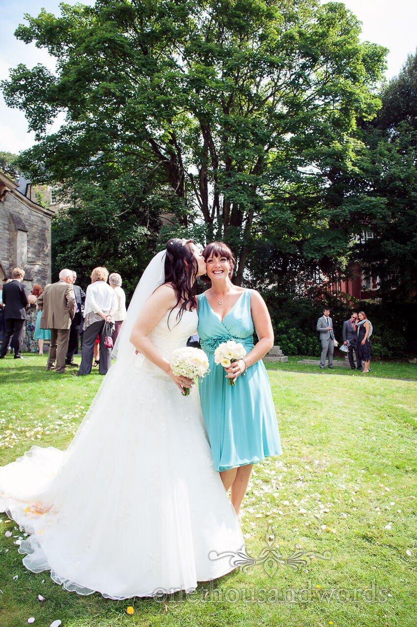Bride kisses Bridesmaid in green bridesmaids dress in church gardens