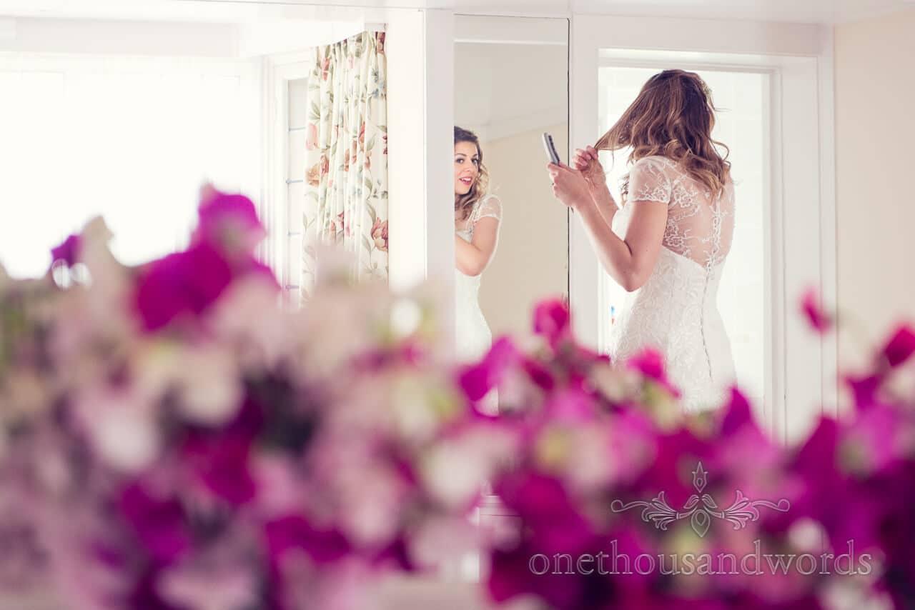Bride portrait in mirror with wedding flowers