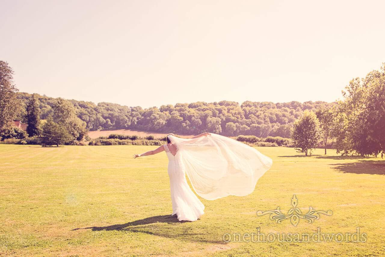 bride runs in countryside with large veil