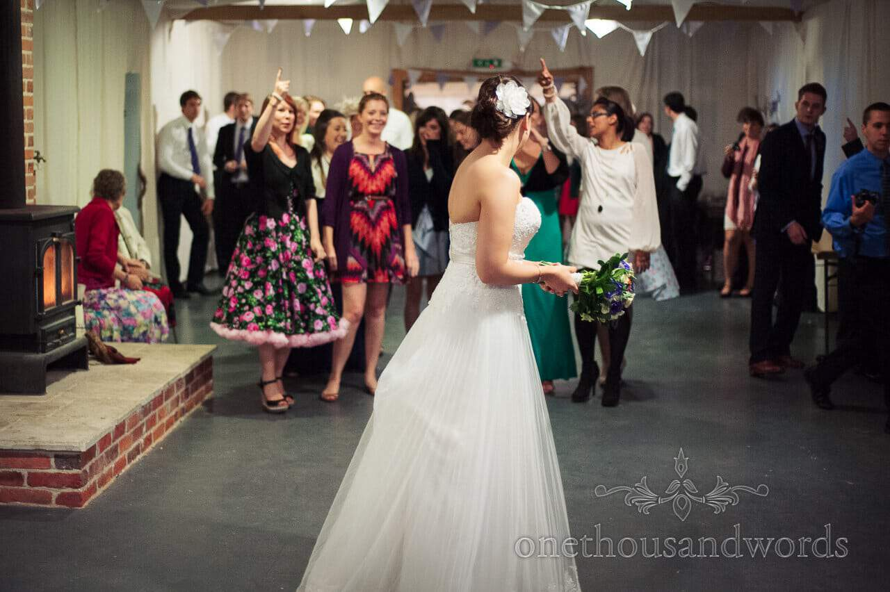 Bride throws wedding bouquet at Carpenters Barn, New Forest