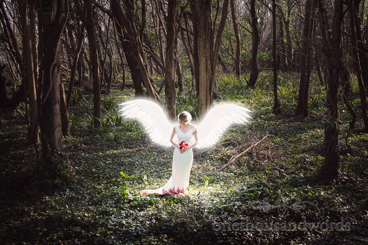 Bride with angel wings in woodland