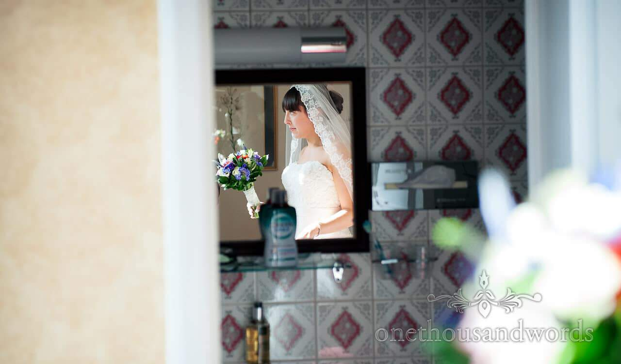 Bride with wedding bouqet in mirror at The Crown Manor House Hotel Lyndhurst