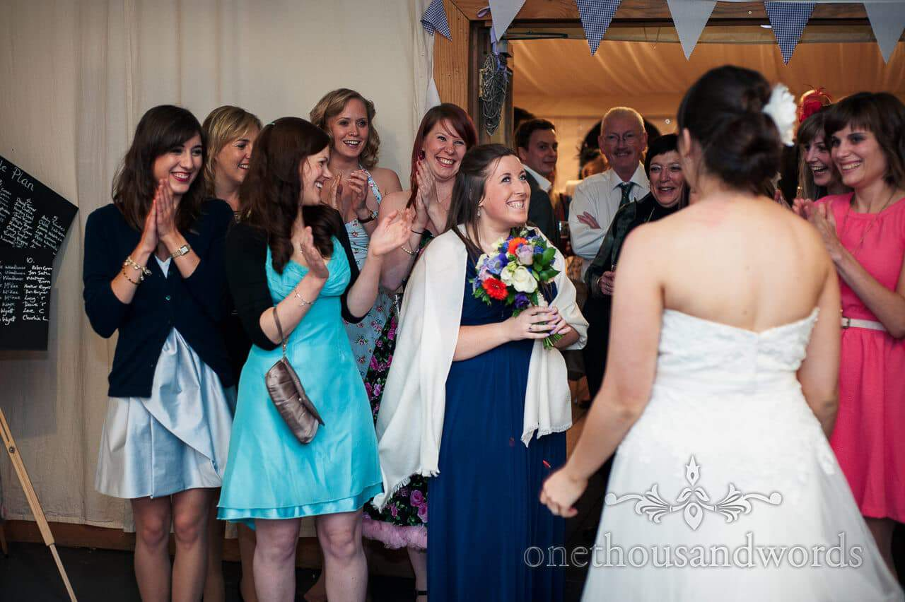 Bridesmaid catches wedding bouquet at Carpenters Barn wedding