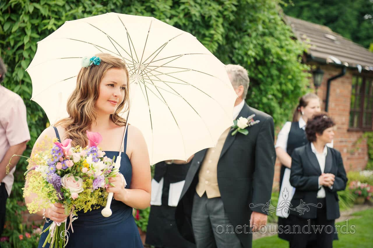 Bridesmaid with ivory wedding parasol and countryside wedding bouquet