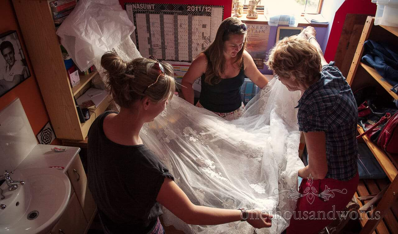 bridesmaids and mother of the bride prepare lace wedding dress
