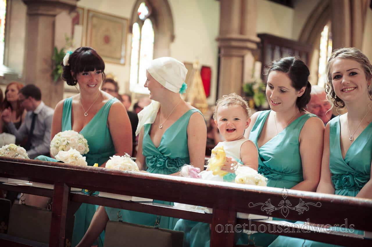 Bridesmaids and flower girl in green bridesmaids dresses in church