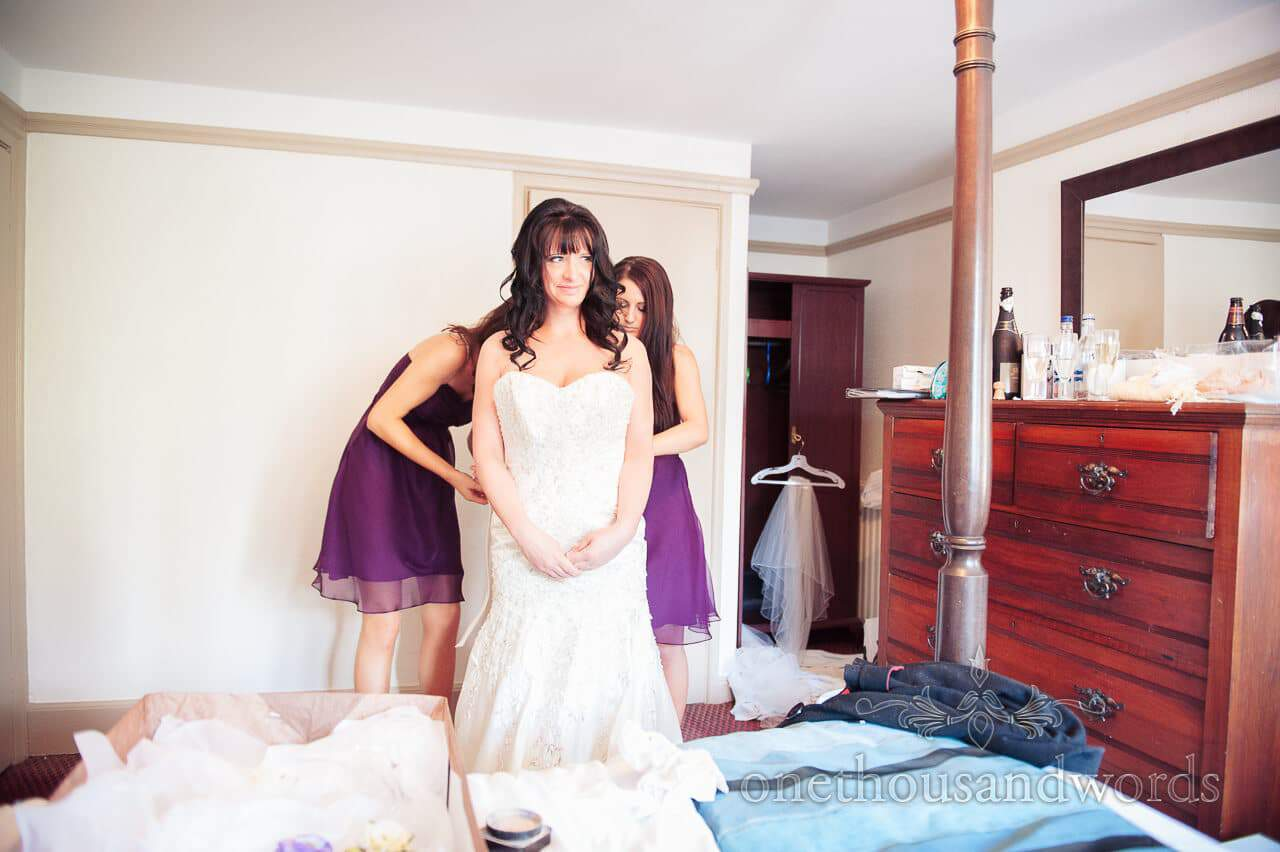 Bridesmaids help bride into wedding dress at The Bankes Arms Hotel