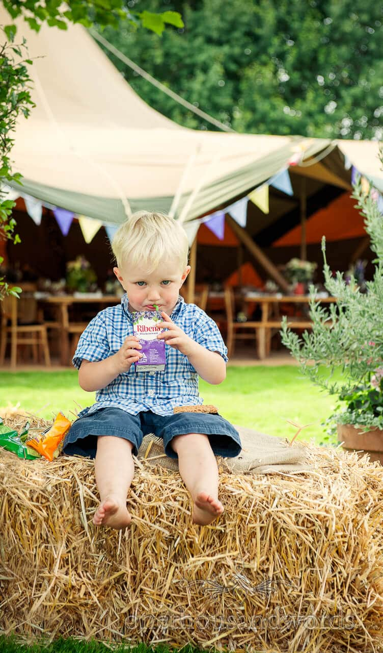 child wedding guest in front of countryside wedding tipi