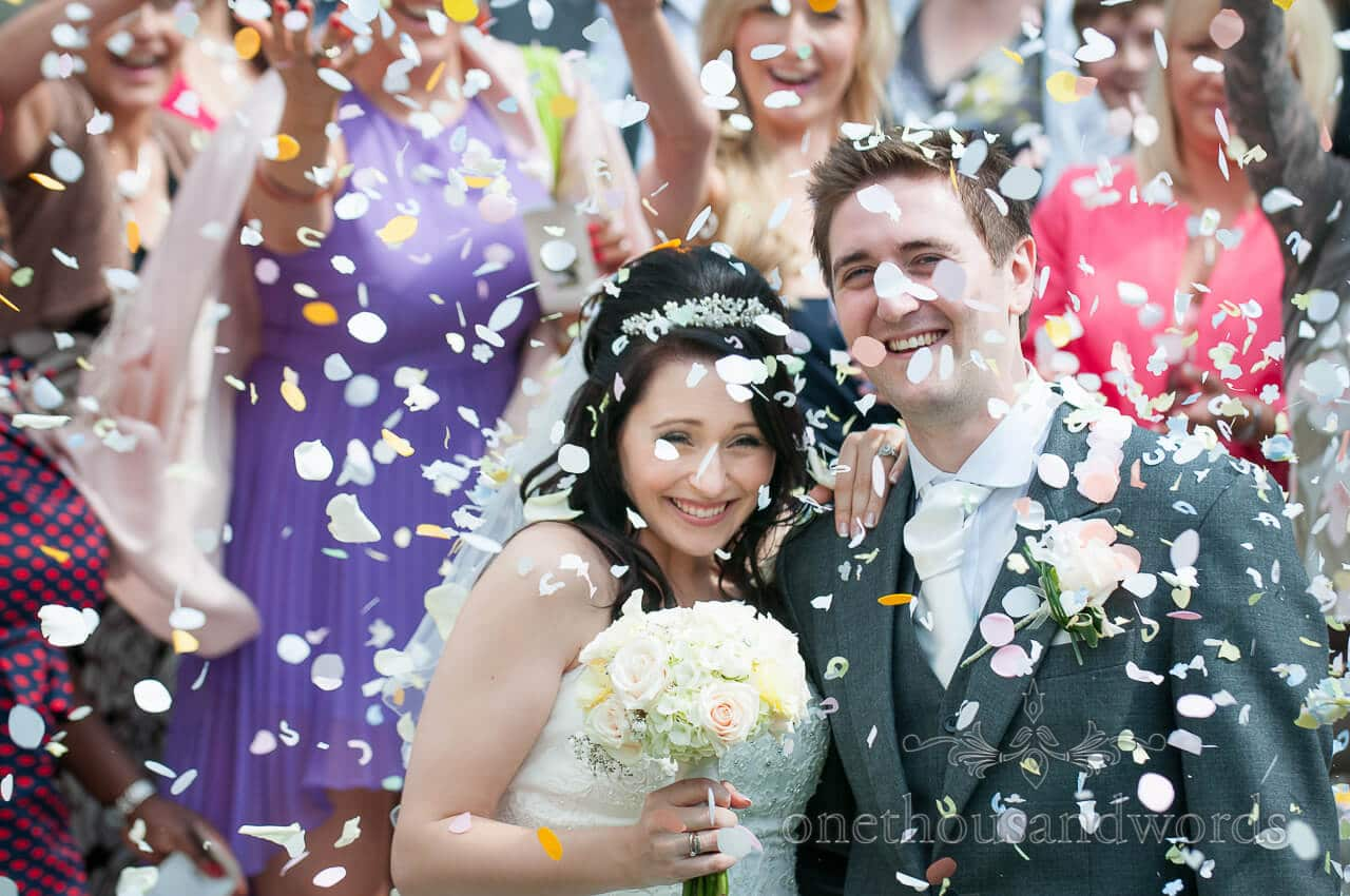 Bride and groom with shower of wedding confetti at Bournemouth church