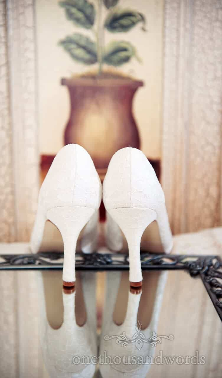 detailed lace wedding shoes on mirror