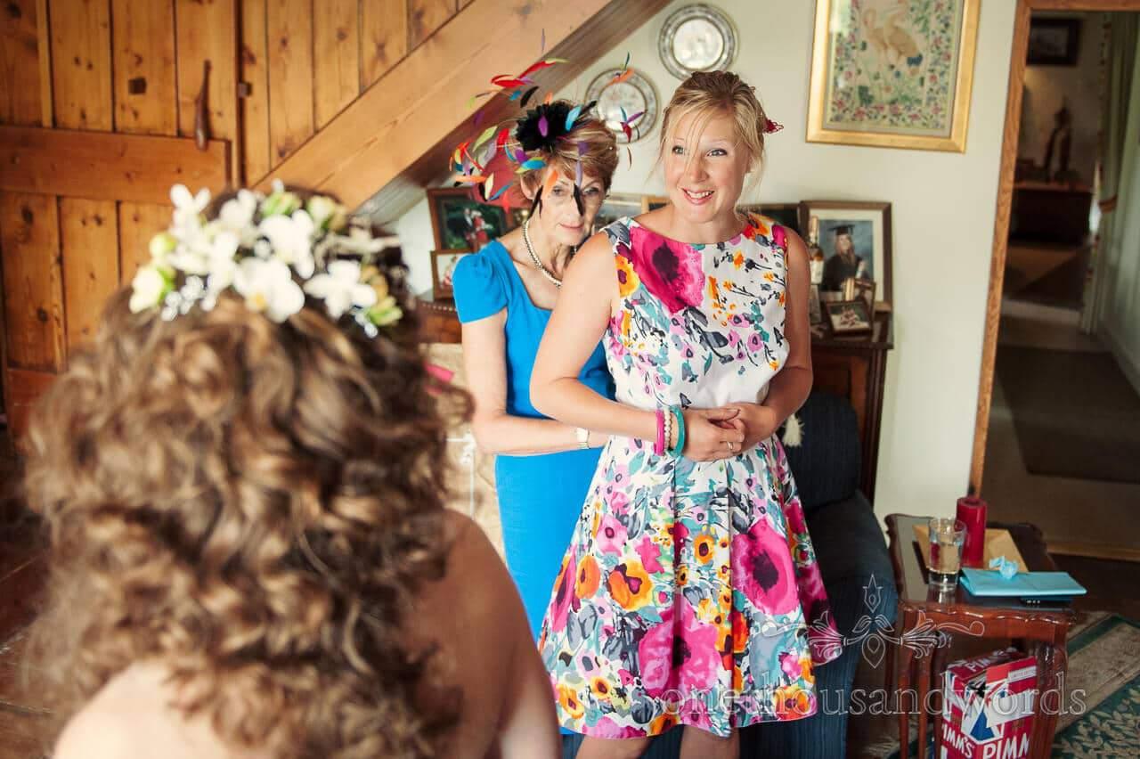 Floral bridesmaid dress adjusted on wedding morning