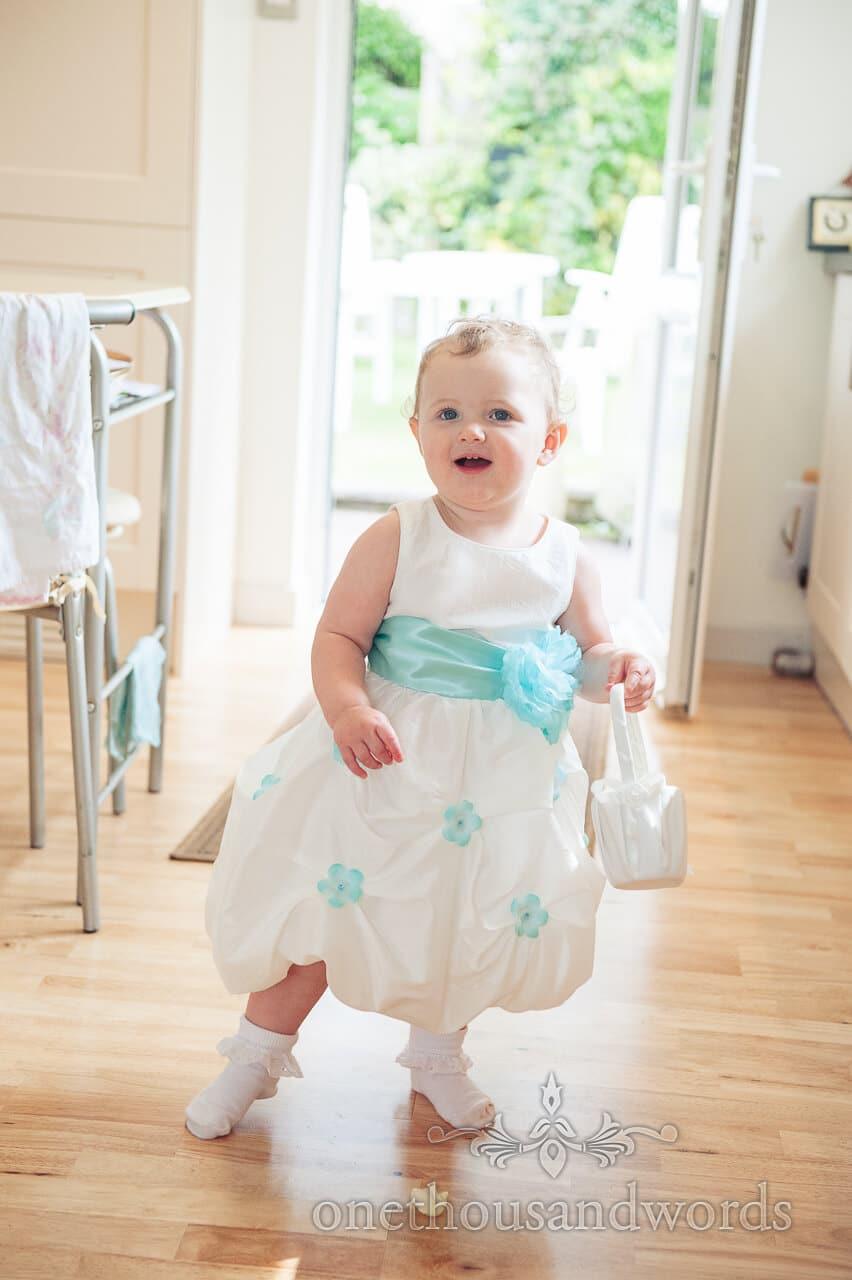 Cute flower girl wears blue and white flower girl dress with flower pattern
