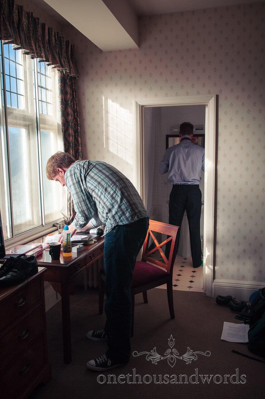 Groom adjusts his speech in hotel on wedding morning