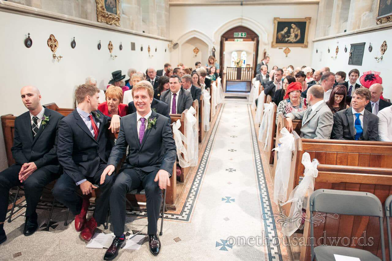 Groom and guests await bride at church wedding service
