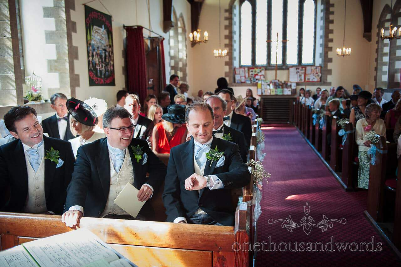 Groom checks his watch at Dorset church wedding ceremony