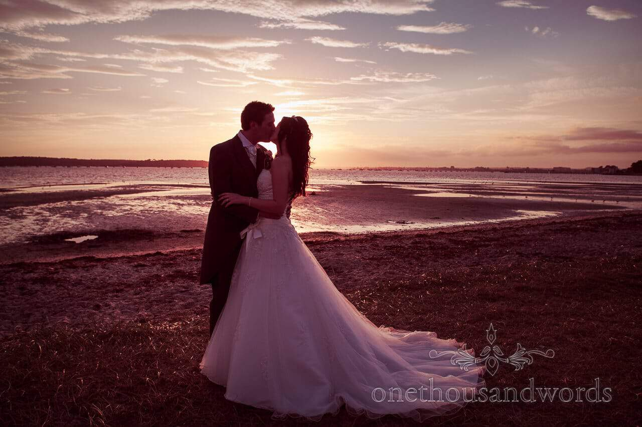 Kiss on the beach at Poole Hotel wedding