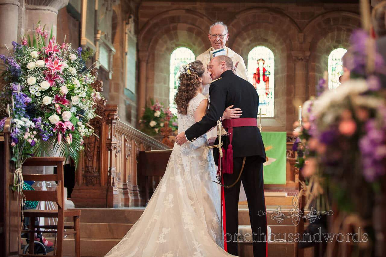 military wedding photographs of bride and groom kissing in church