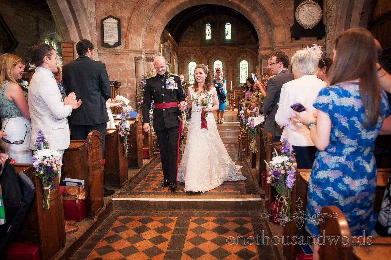 Military wedding photographs of bride and groom walking down church aisle