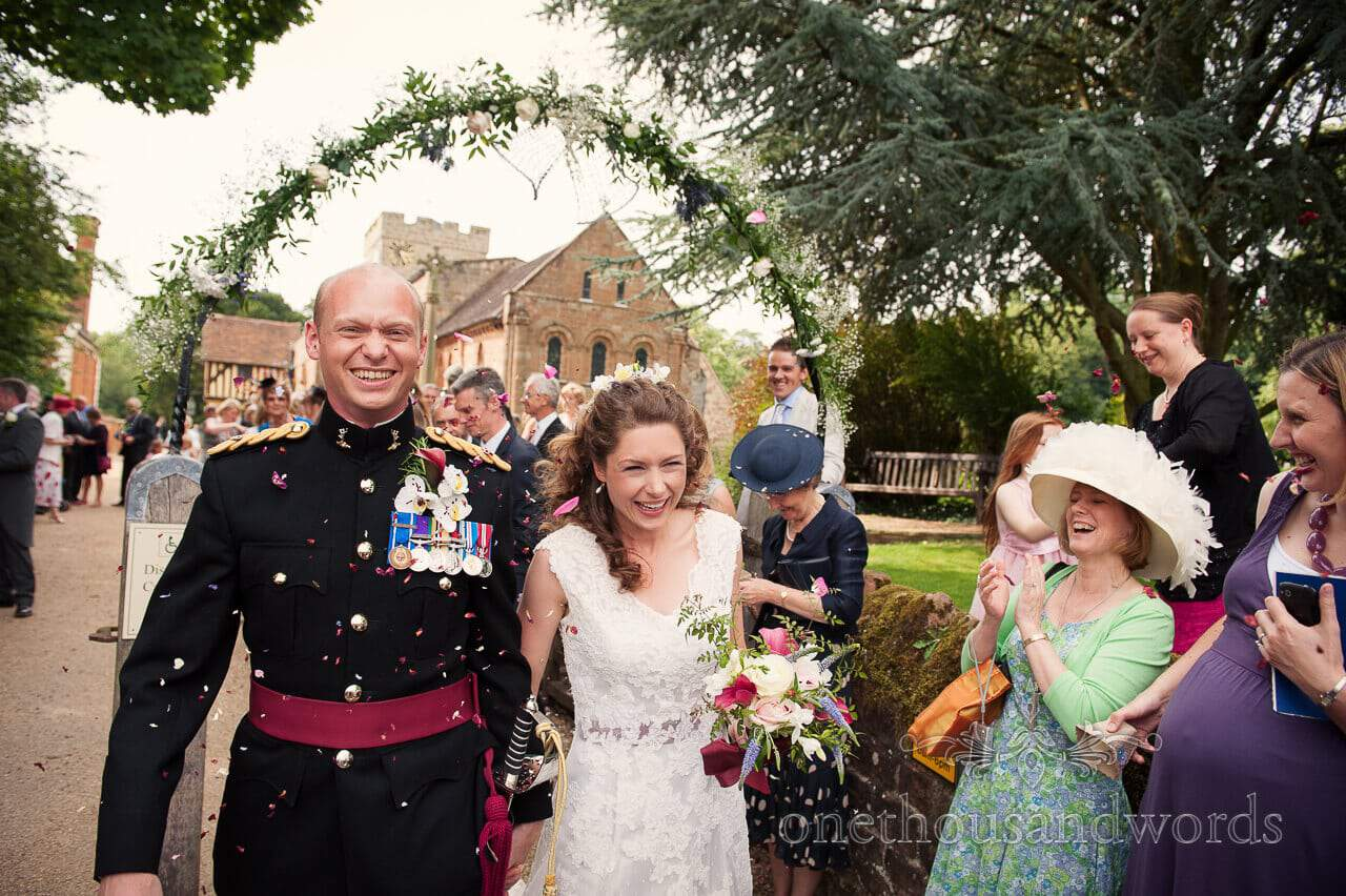 Military wedding photographs of wedding confetti and floral archway