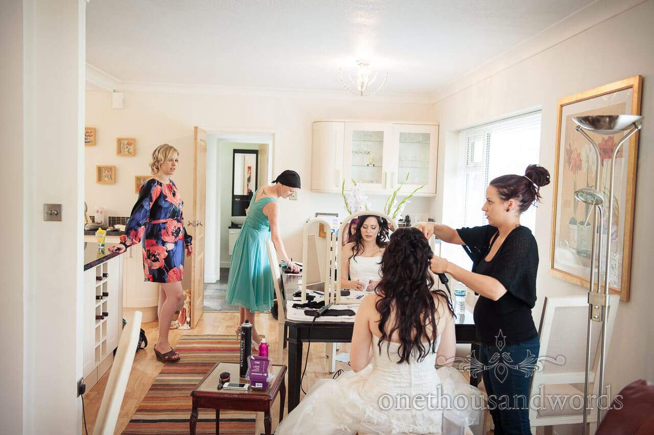Wedding morning preparations at brides home with hairdresser