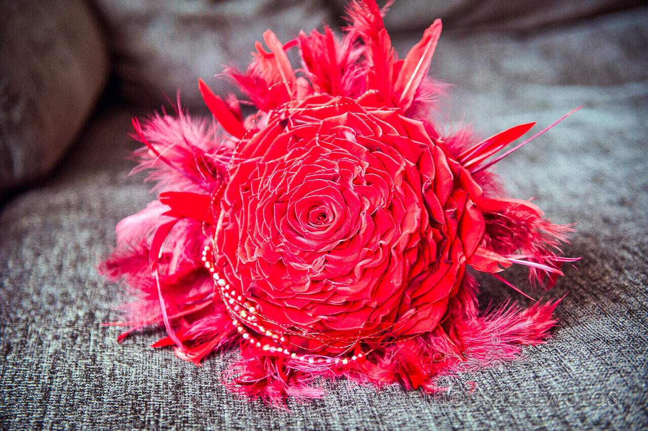 Red rose wedding bouquet with red feathers