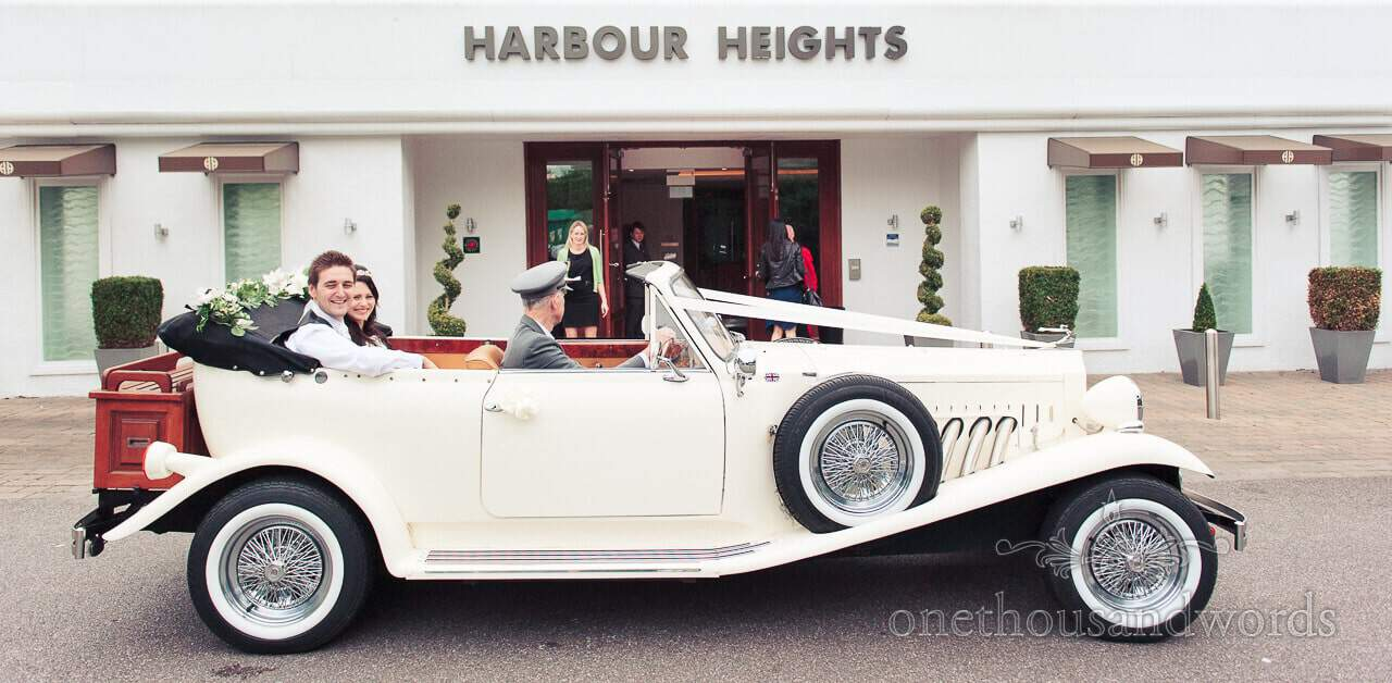 Wedding couple arrive at Poole Hotel wedding in classic car
