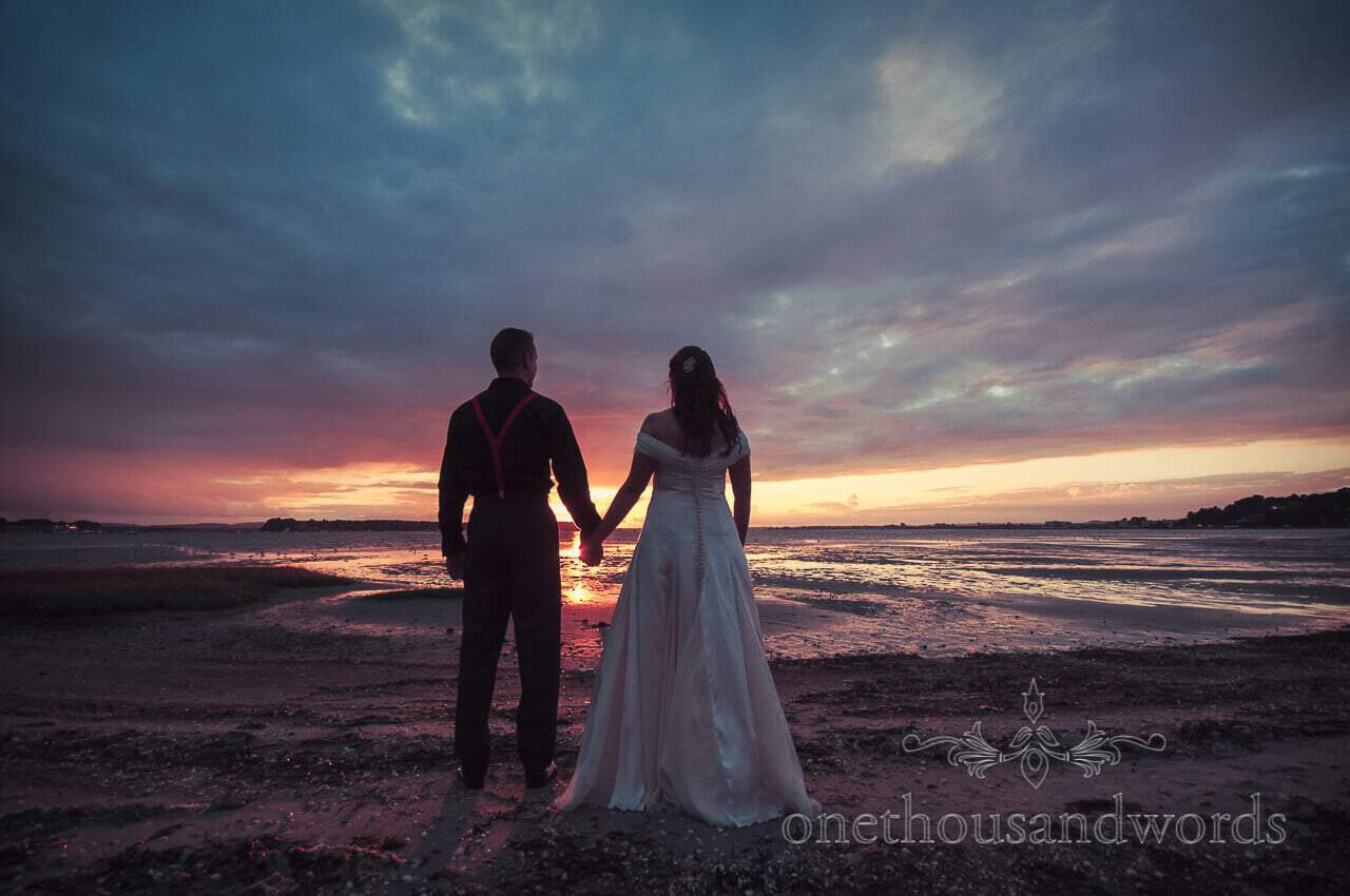 Wedding couple hold hands with beach sunset