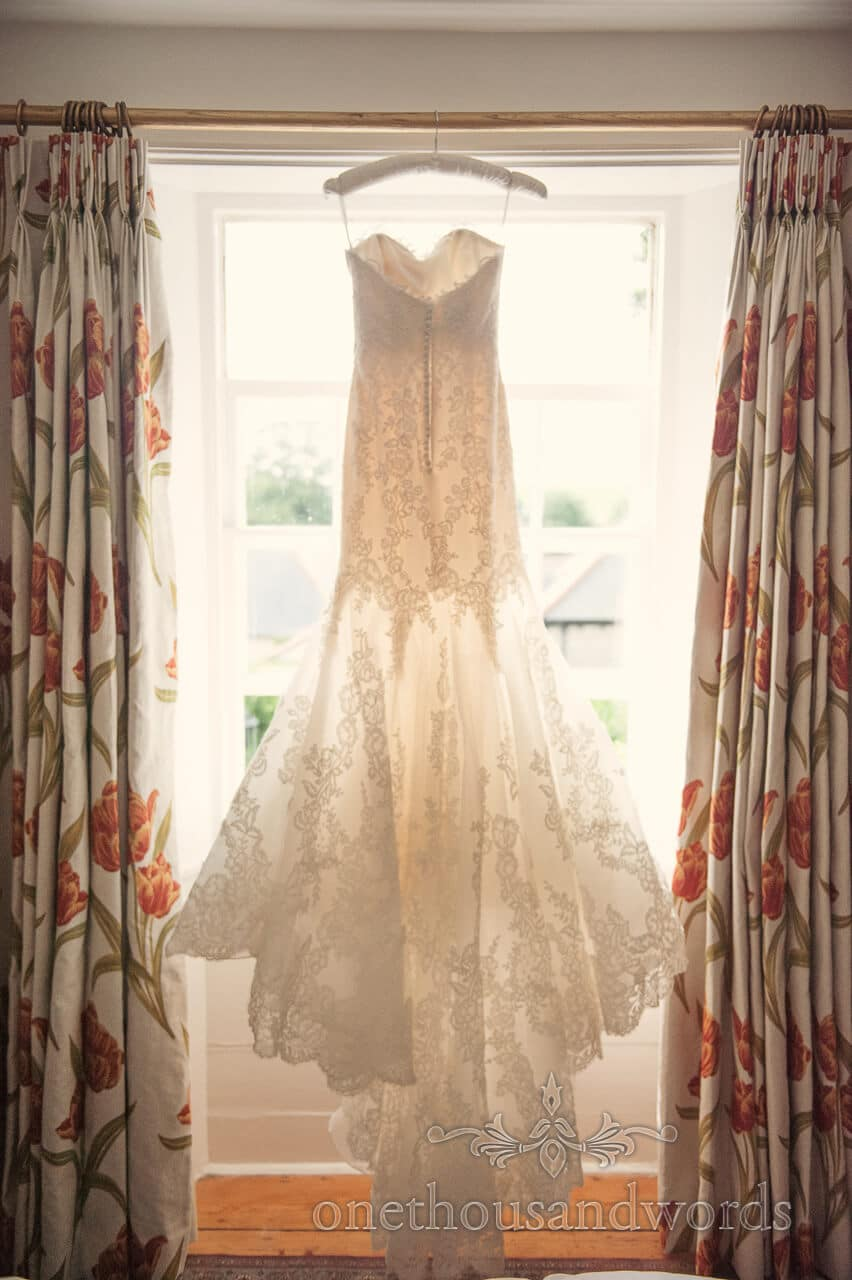 Wedding dress with detail hanging in window for Plush Manor Wedding