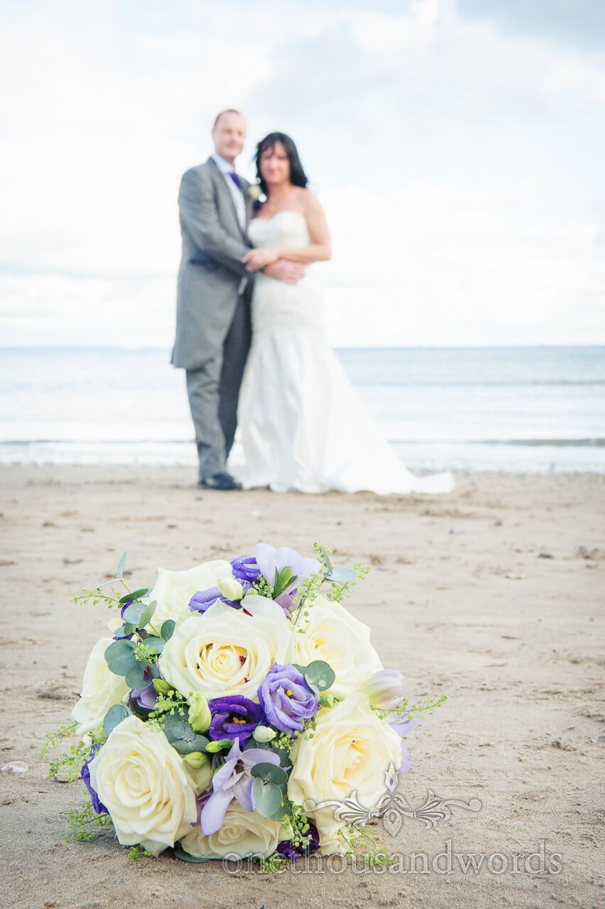 cream and blue wedding flower bouquet on Dorset beach with bride and groom