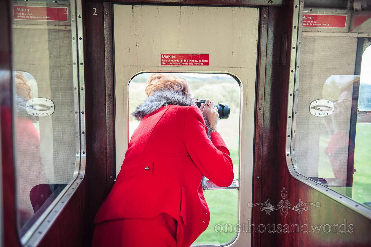 Wedding guest takes photographs on Swanage Steam train