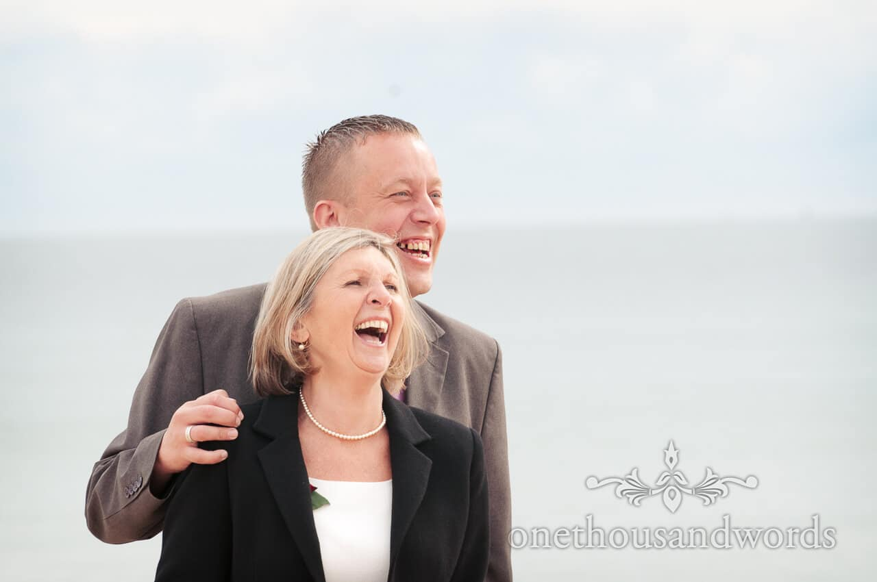 wedding guests laugh on beach at Sandbanks Hotel