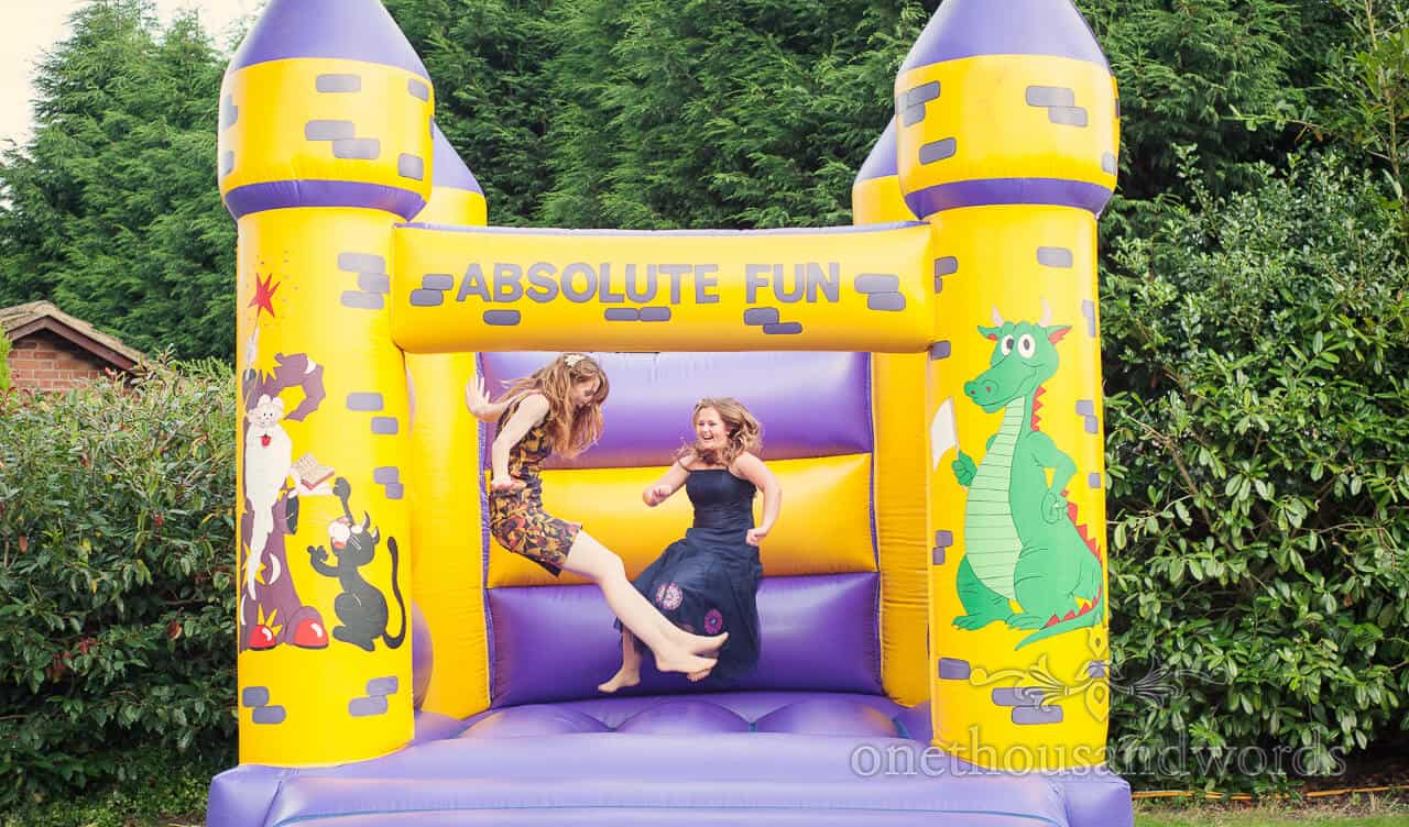 wedding guests on bouncy castle at wedding