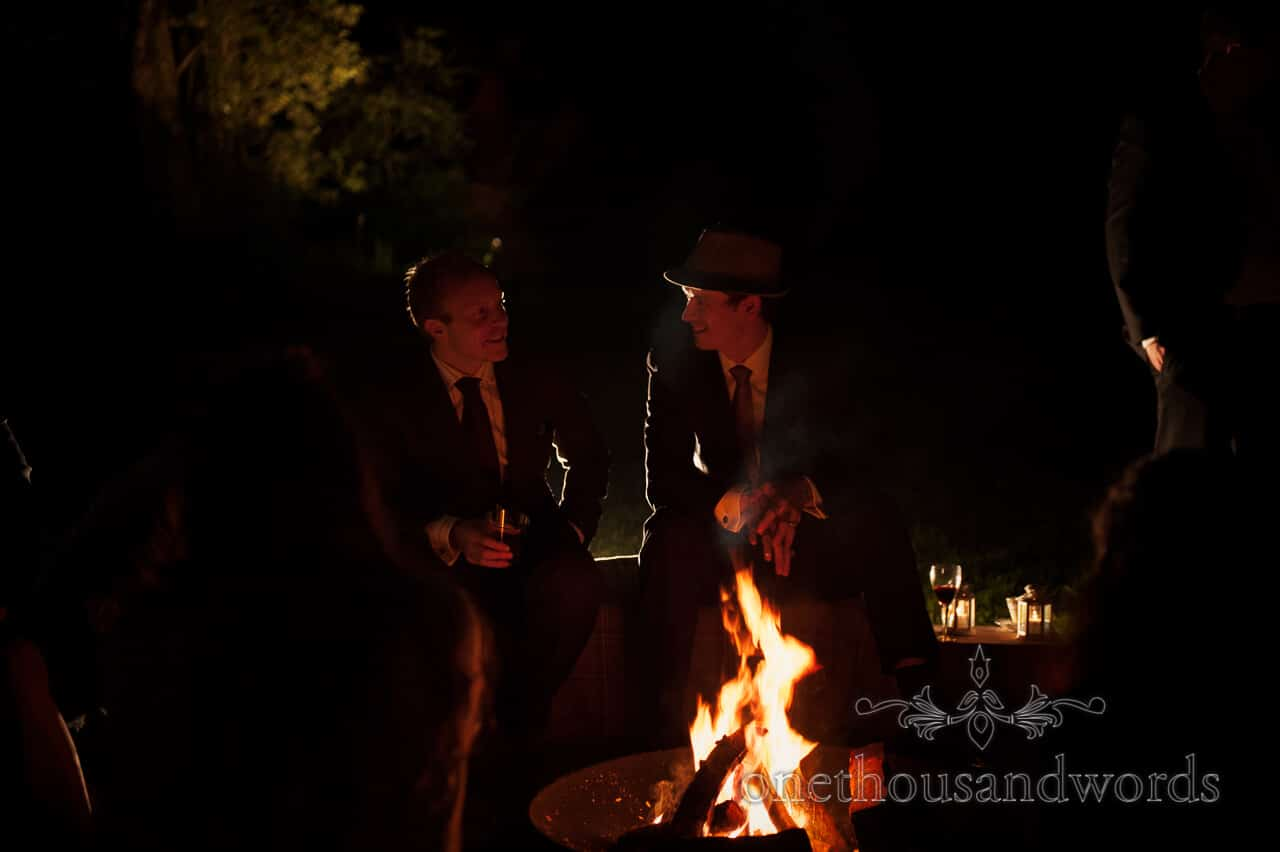 Wedding guests sit by campfire on wedding evening at Plush Manor