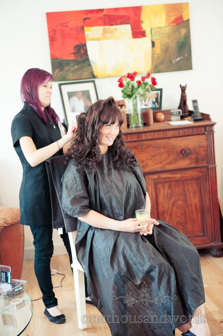 Bridesmaid has weddign hair stlyed during bridal preparations