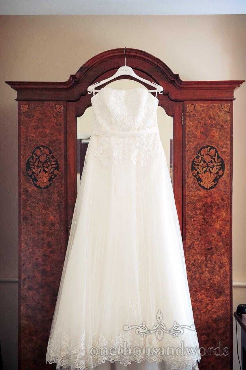 White wedding dress hanging on antique wardrobe