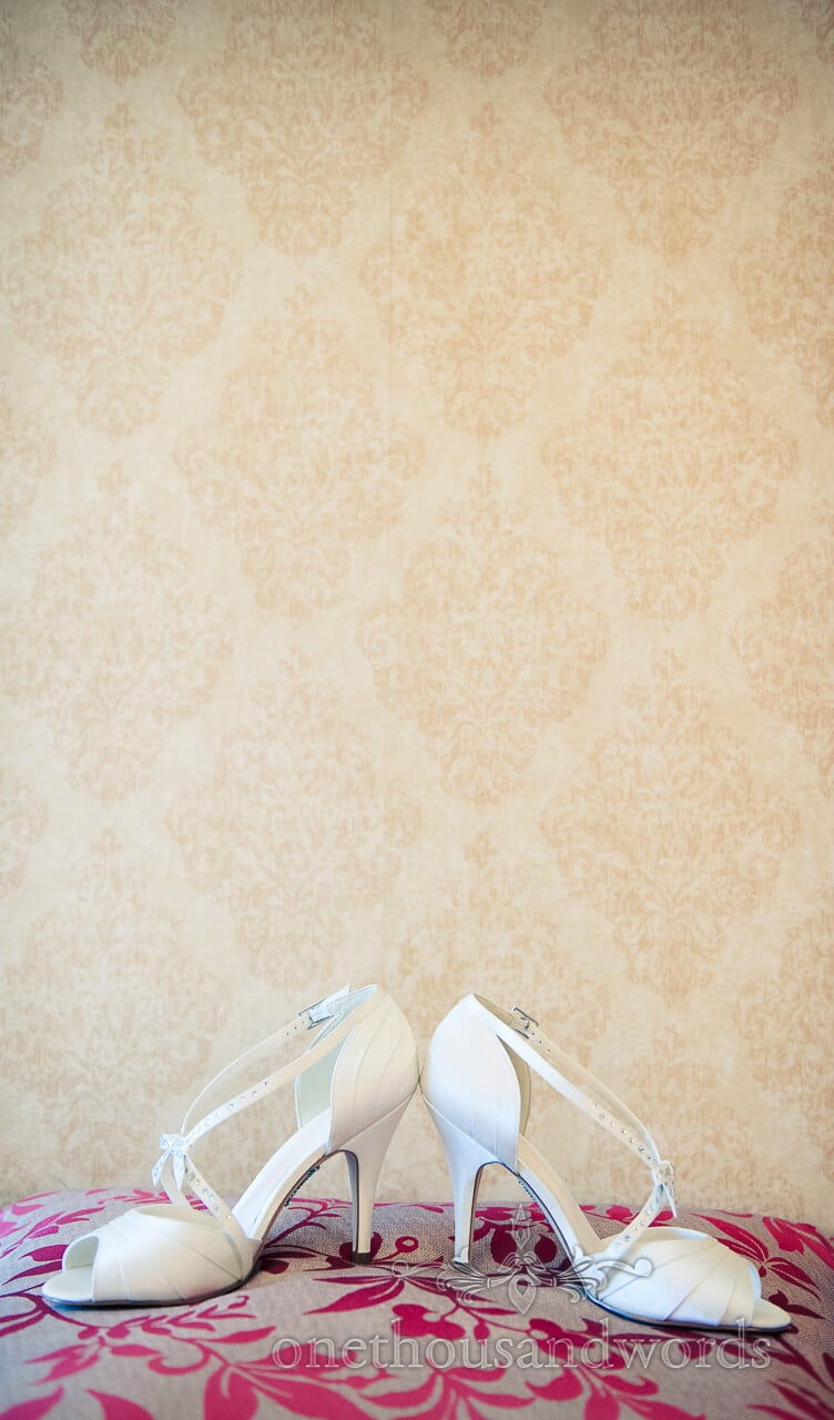 White Wedding shoes on pillow with damask wall paper
