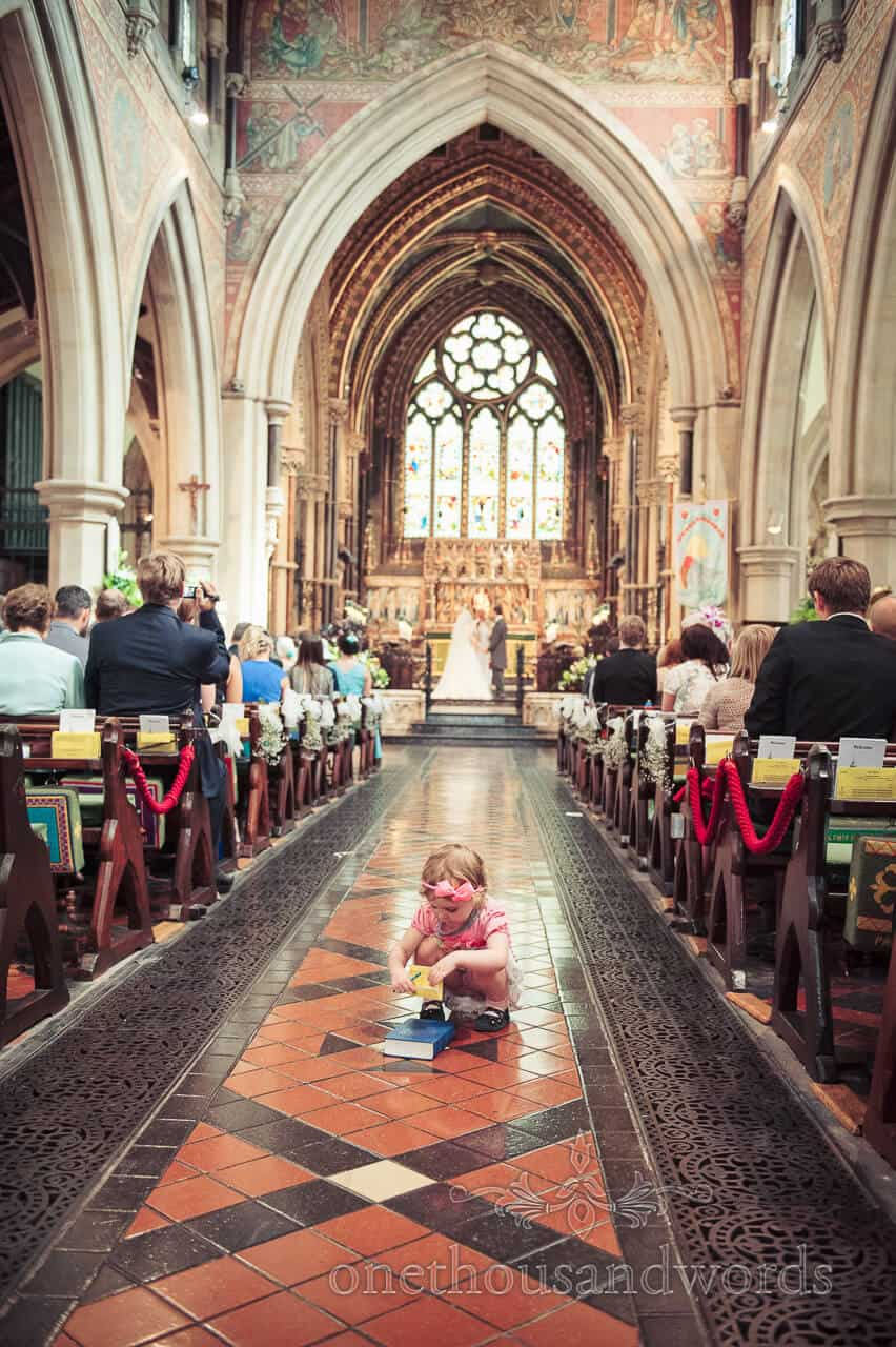 Child wedding guest plays in the aisle at Bournemouth church wedding