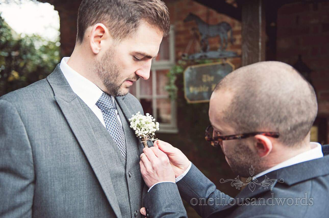 Best men put on button hole on wedding morning