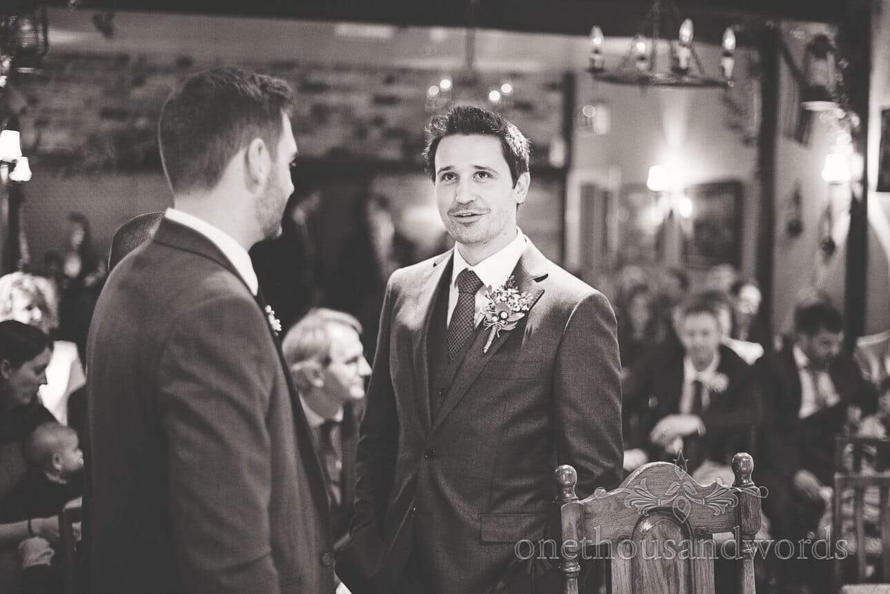 Black and white wedding photograph of groom awaiting bride