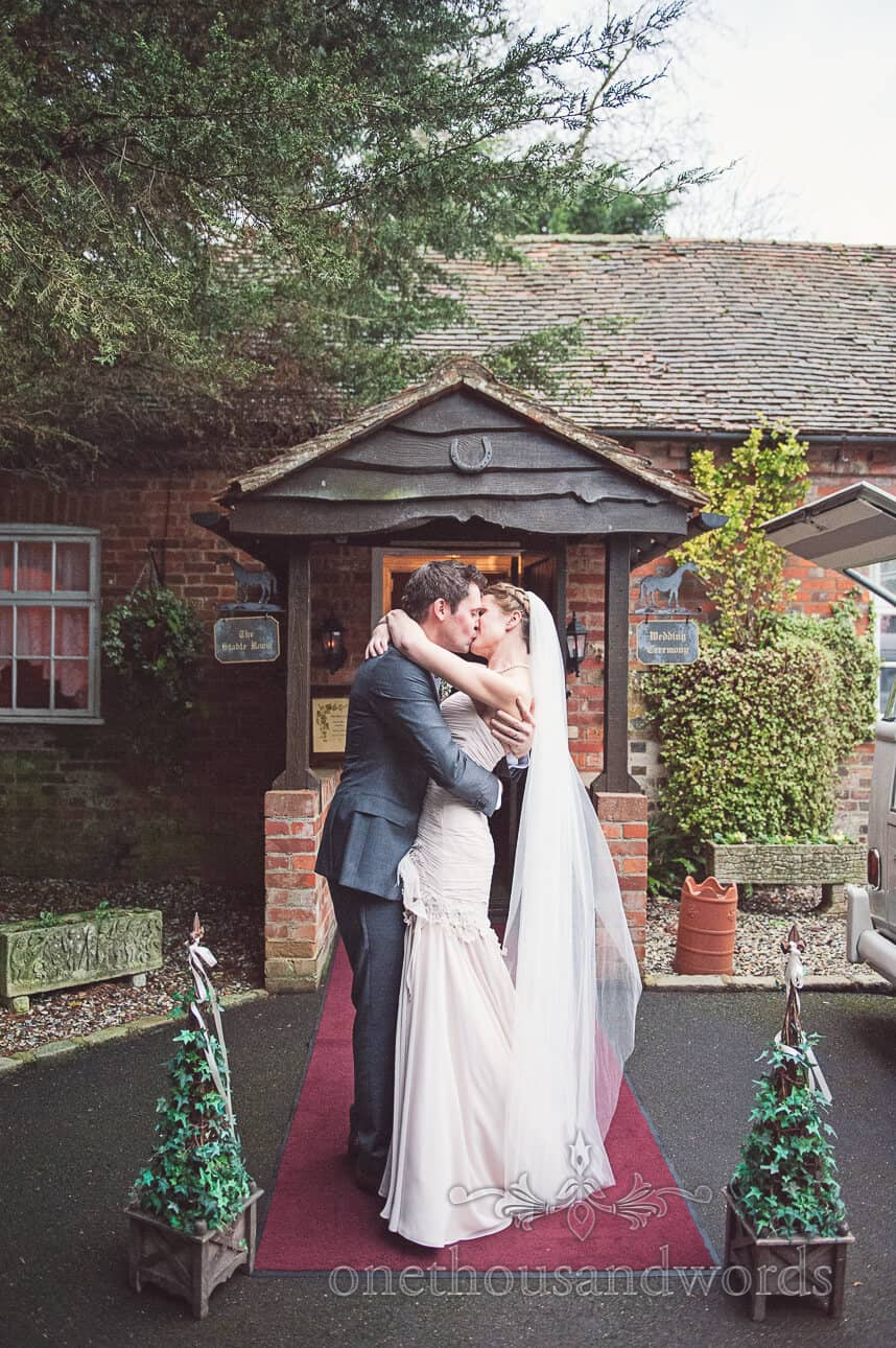 Bride and Groom kiss outside Old Mill wedding venue in Berkshire